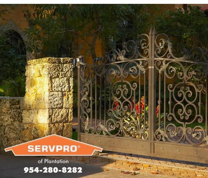 Ornate iron gates and tropical foliage mark the entrance to a large Plantation, Florida residence.