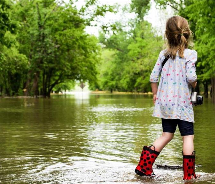 Little Girl Walking through flooded street with red rain boots on